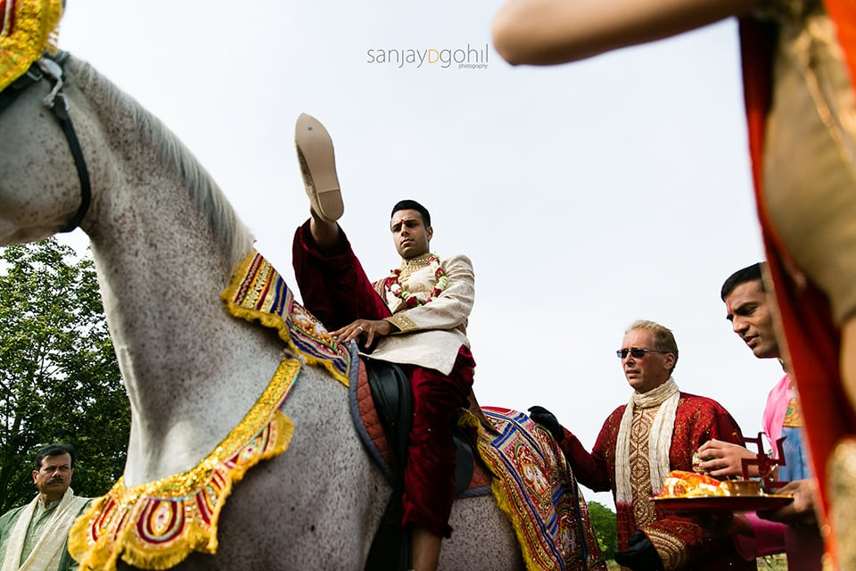 Wedding groom getting off horse