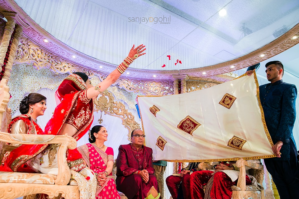 Bride throwing petals during gujarati wedding ceremony