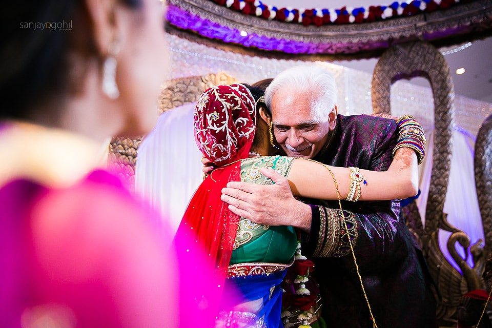 Bride hugging father during wedding ceremony