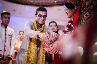 Bride's brother giving seeds into the bride and groom's hands