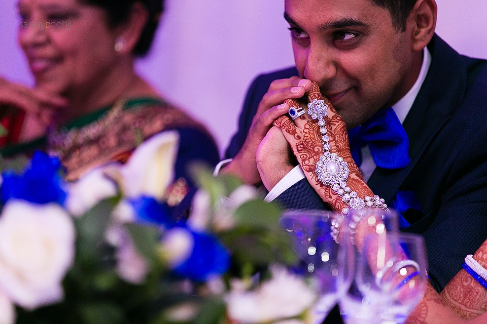 Closeup of groom holding bride's hands