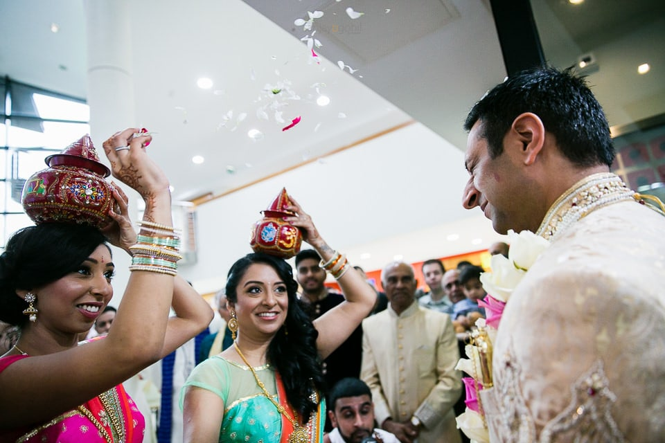 Asian wedding groom being showered with flowers