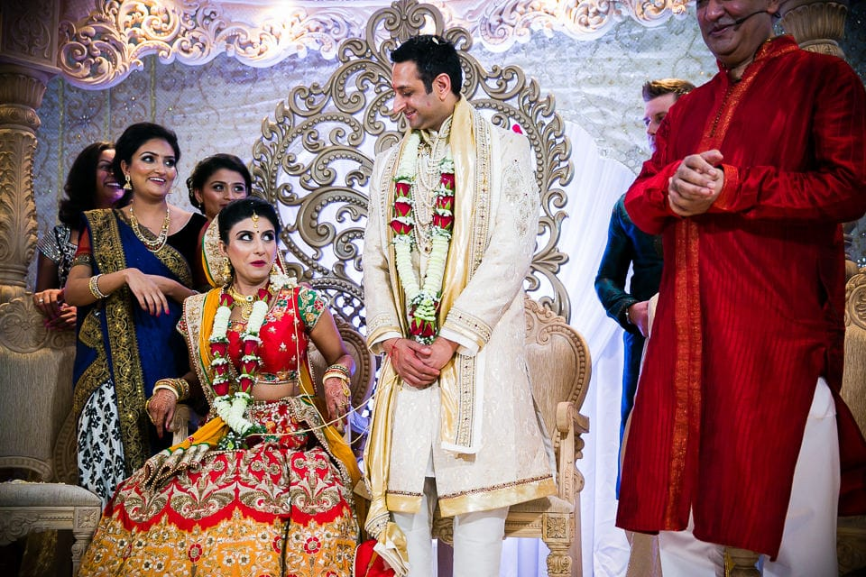 Bride sits down before groom during gujarati wedding ceremony