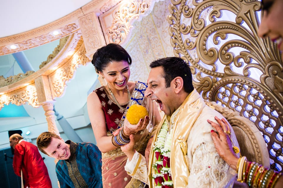 Groom being fed huge sweet during wedding