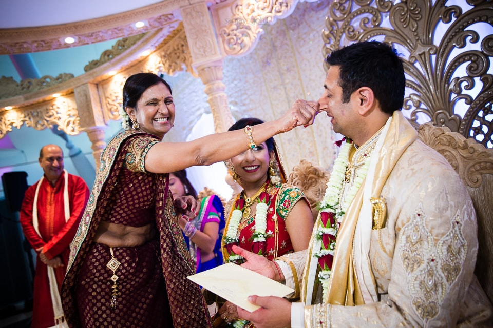 Groom's nose being pinched during gujarati wedding ceremony