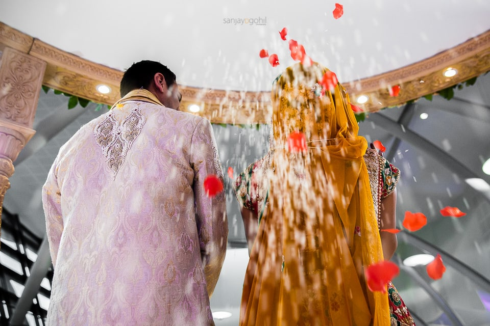 Bride throwing rice and flowers behind her