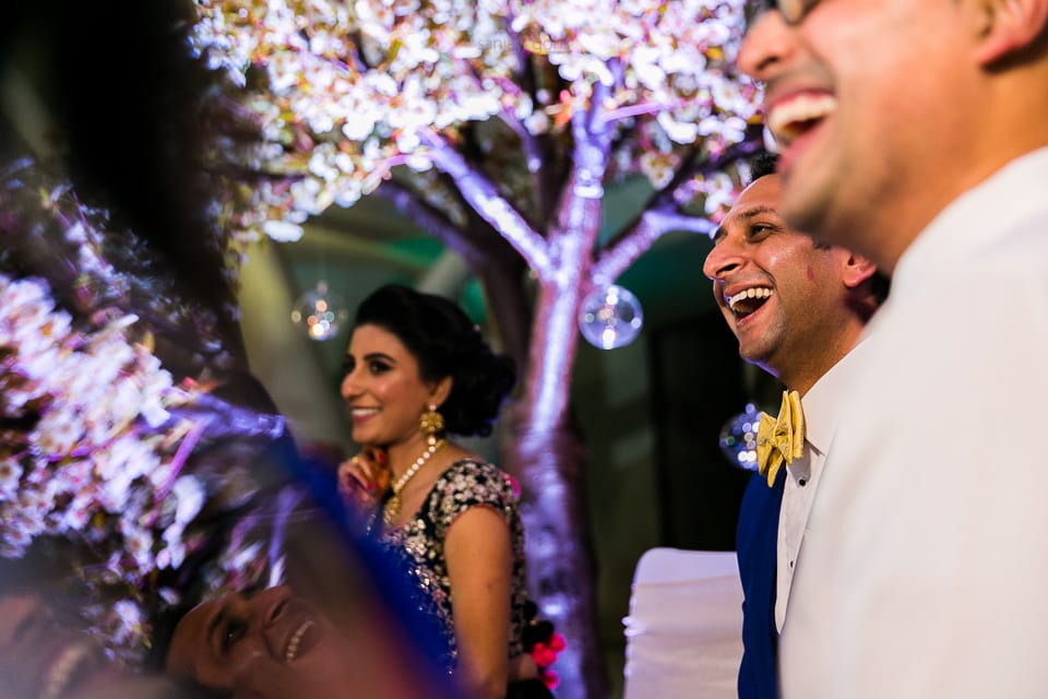 Bride and grooms laughing during speechs at reception party