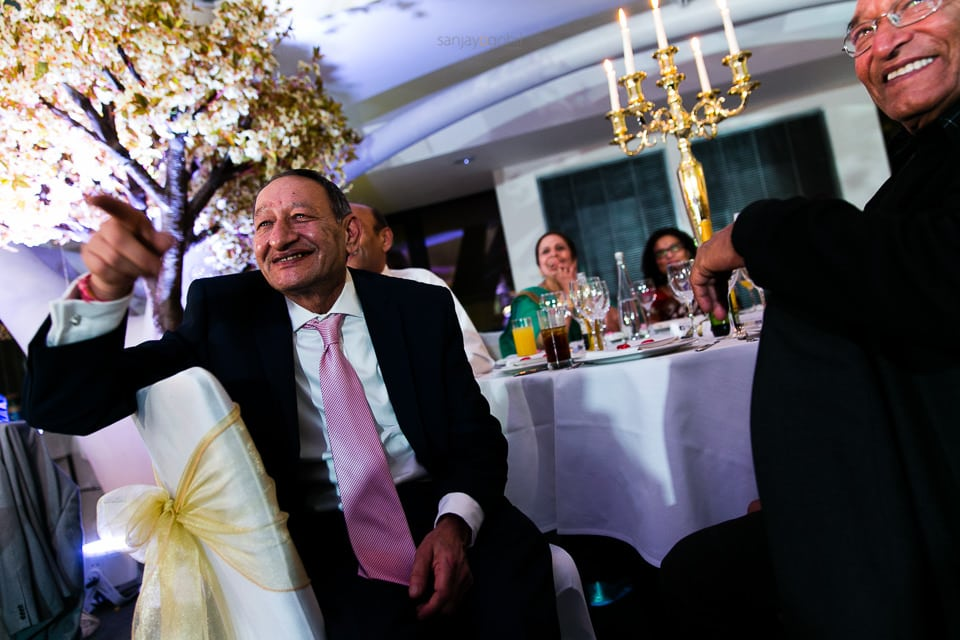 Wedding guests laughing during speechs at reception party