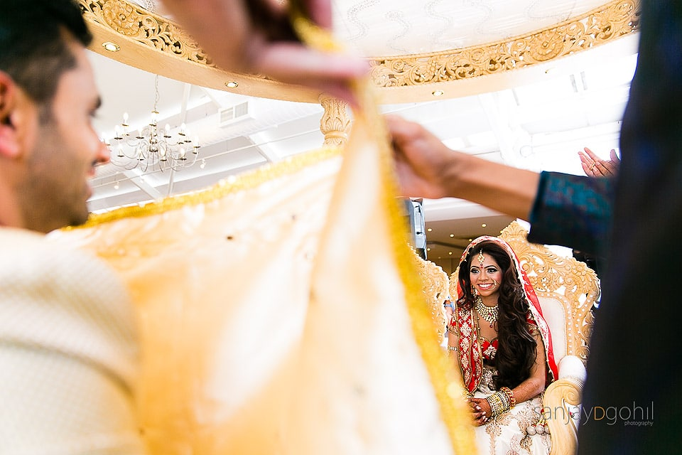 Hindu Wedding Bride laughing as the antarphat is lowered