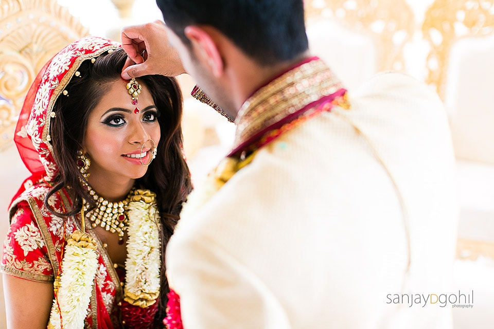 Groom placing Sindoor into the parting of the brides' hair