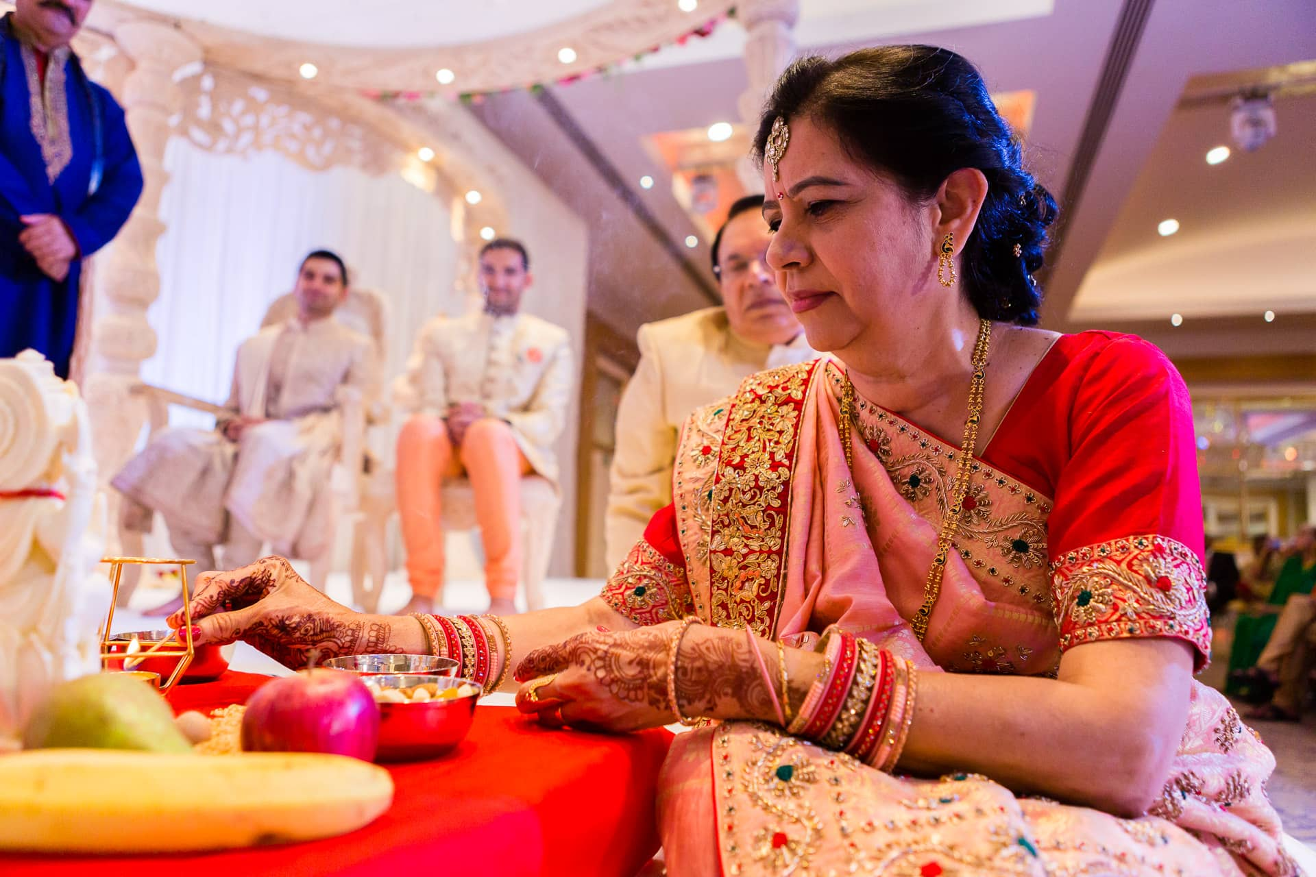 Mother of the bride lighting candle during Hindu wedding ceremony