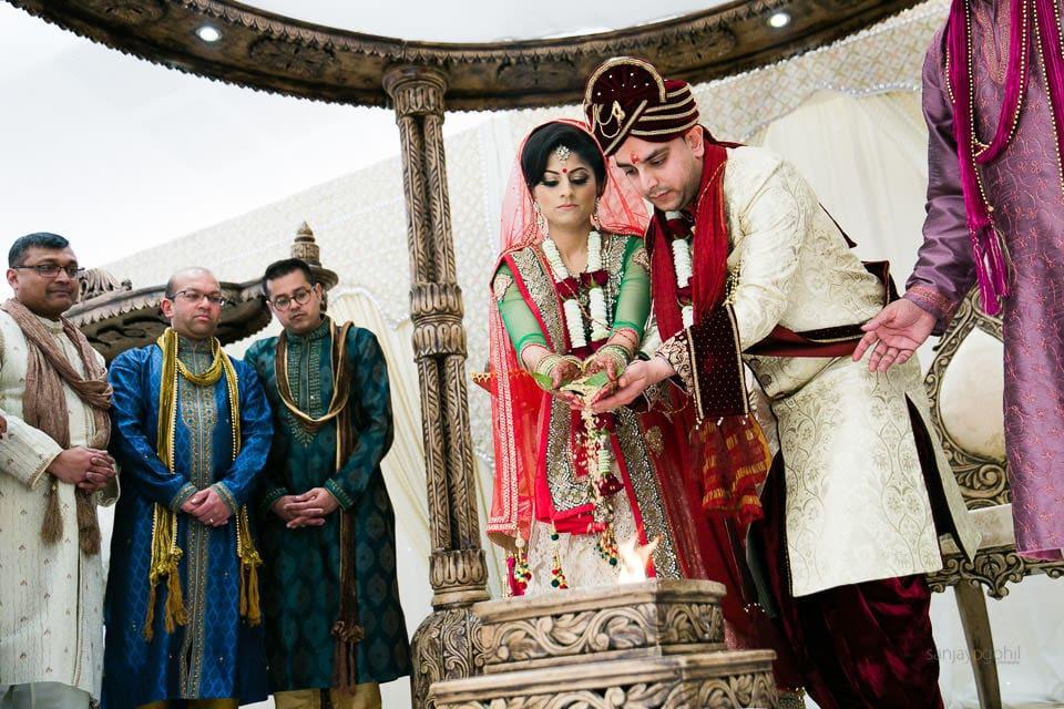 Bride and groom placing seeds into the Havan