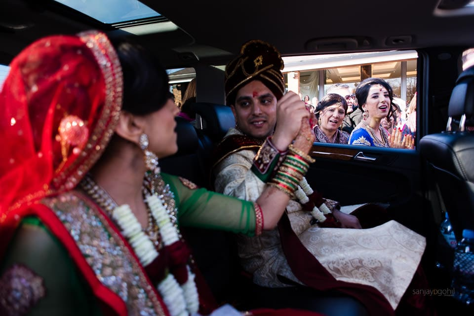 Bride and groom holding hands in the wedding car
