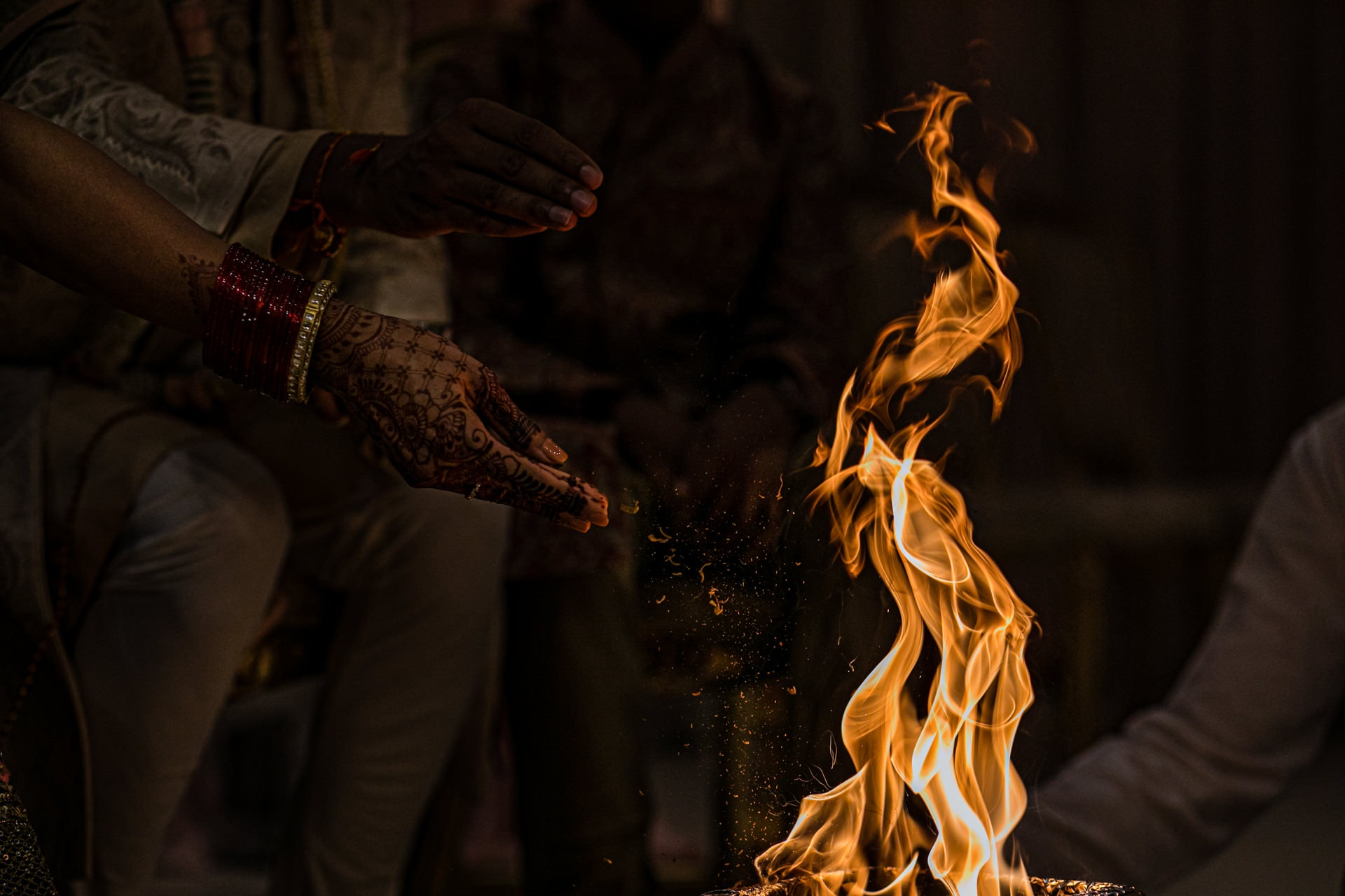 Seeds being thrown into the fire during Asian wedding ceremony