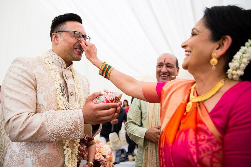 Hindu wedding groom's nose being pinched