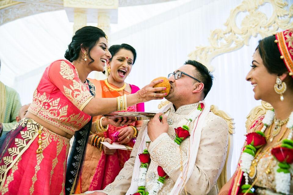Bride's sister feeding groom
