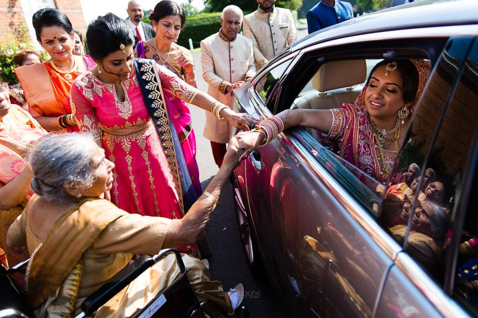 Bride holding grandmother's hand before leaving