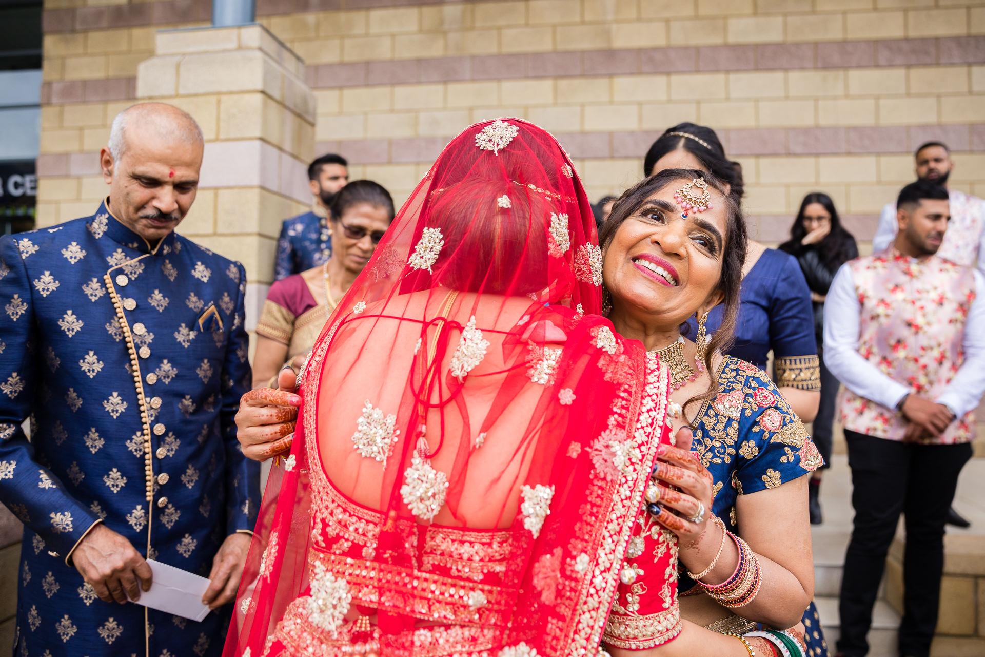 Bride hugging parents after wedding