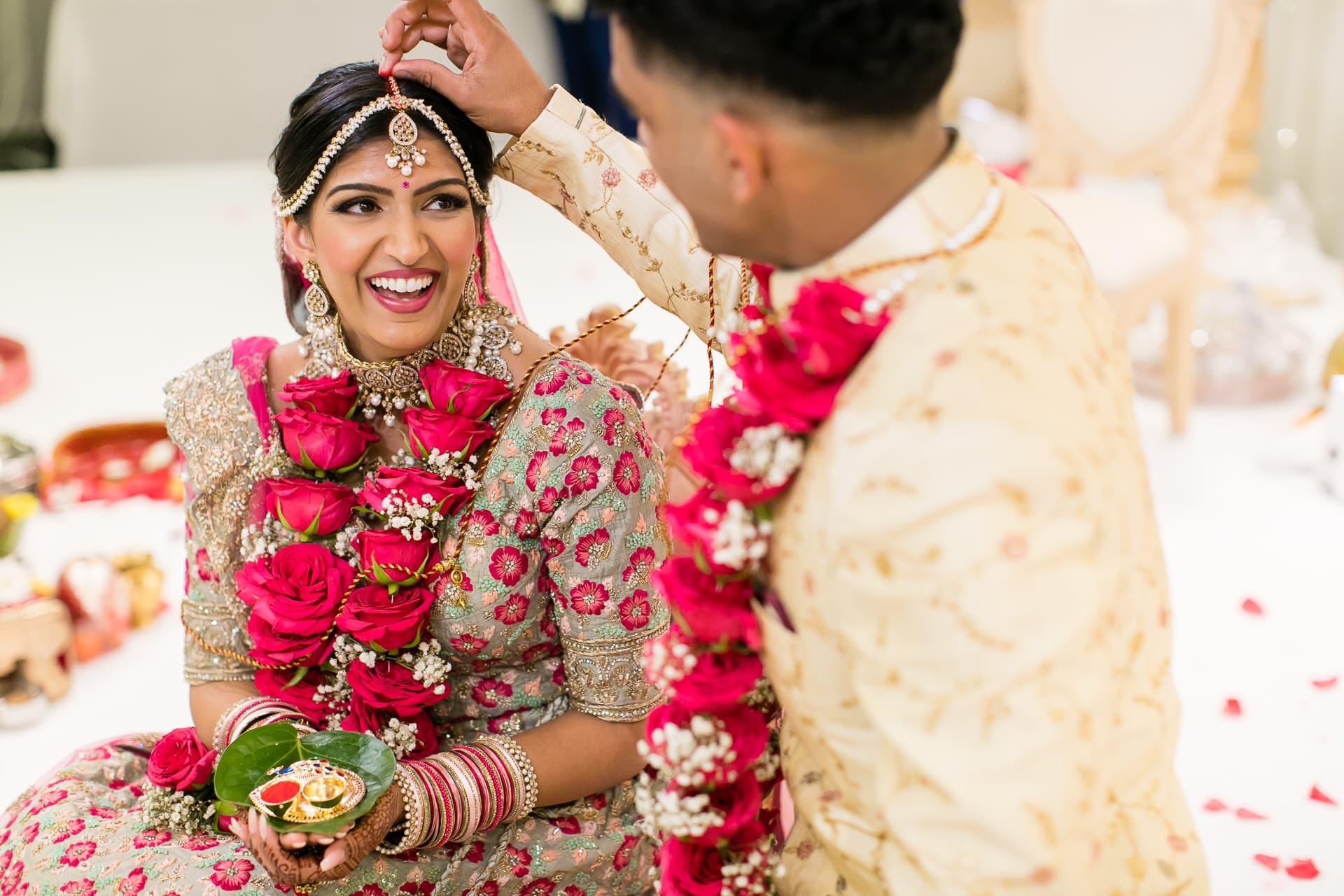 Groom placing sindoor into parting of bride's hair